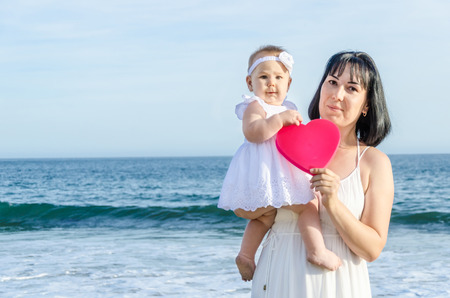 Mother and her baby girl on the sandy beach near ocean in sunny day/Mothers day concept