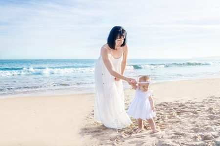 Mother and her baby girl on the sandy beach near ocean in sunny day//first steps/ step by step