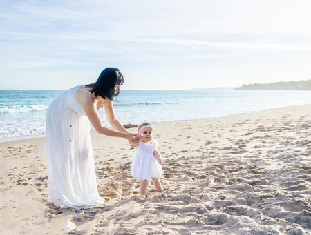 Mother and her baby girl on the sandy beach near ocean in sunny dayfirst steps step by step