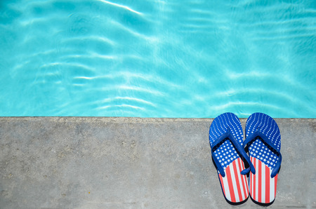 Summer background with flip flops of American flag colors and pattern near the swimming pool Stock Photo