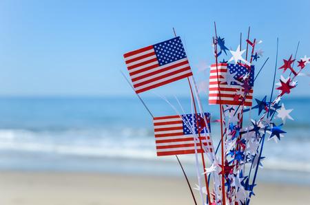 Fondo patriótico de Estados Unidos con banderas y decoraciones en la playa de arena Foto de archivo