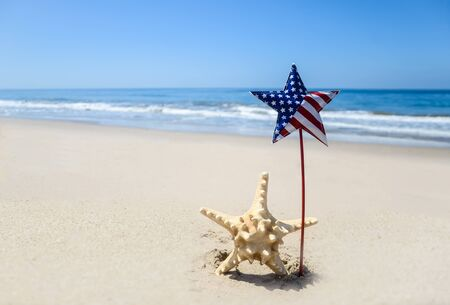 Patriotic USA background with starfish decorations on the sandy beach