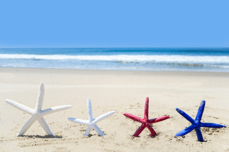 Patriotic USA background with white, red and blue starfishes on the sandy beach