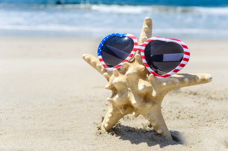 Patriotic USA background with starfish in the sunglasses on the sandy beach Stock Photo - 78946109