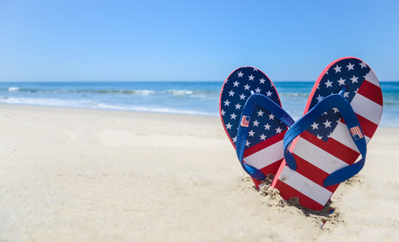 Patriotic USA background with flip flops and decorations on the sandy beach Stock Photo
