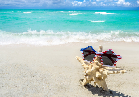 Patriotic USA background with starfish in the sunglasses on the sandy beach