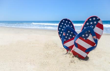 フリップフ ロップと砂浜のビーチの装飾の愛国心が強いアメリカの背景