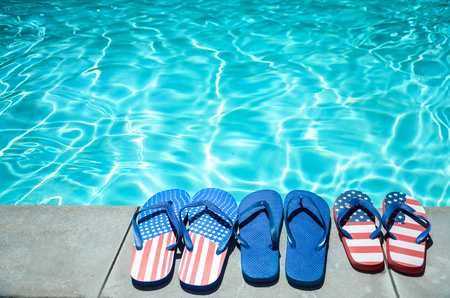 Summer background with flip flops of American flag colors and pattern near the swimming pool Stock Photo - 80228109