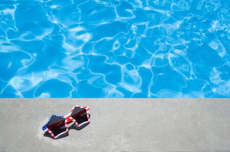 Summer background with sunglasses of American flag colors near the swimming pool