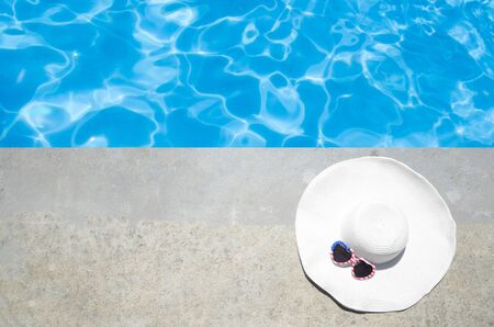 Summer background with white hat and sunglasses of American flag colors near the swimming pool Stock Photo