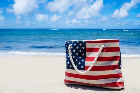 Bag with American flag colors near ocean on the sandy beach - USA patriotic holidays background Stock Photo