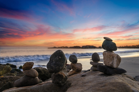 Santa Barbara tropical beach sunset with stacked balanced rocks, piece and harmony concept