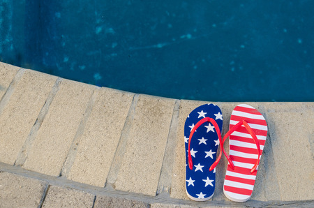 Summer background with flip flops of American flag colors and pattern near the swimming pool Foto de archivo