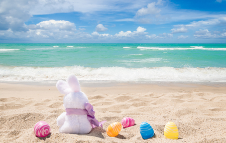 Easter bunny with color eggs on the sandy beach near ocean