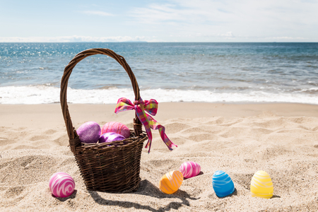 Easter basket with color eggs on the sandy beach near ocean