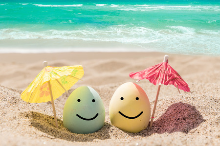 Happy easter background with eggs and coctail umbrellas on the sandy beach near ocean. Stock Photo