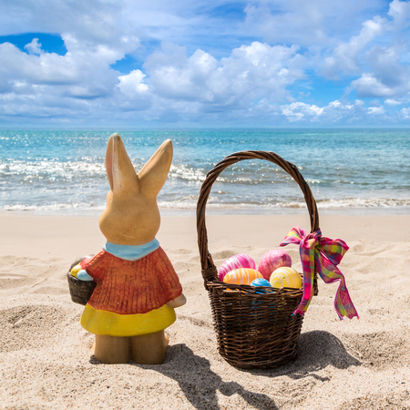 Easter bunny with basket and color eggs on the sandy beach near ocean, square format Stock Photo
