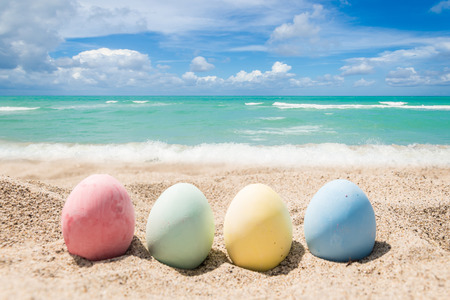 Happy easter background with eggs on the sandy beach near ocean. Stock Photo