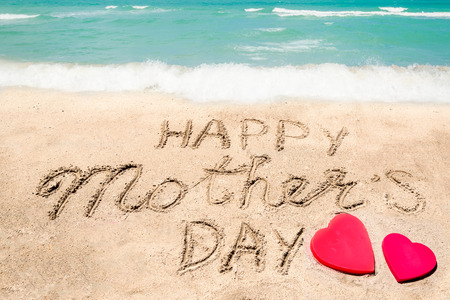 Happy Mother's day background on the sandy beach near the ocean with hearts. Hand drawn lettering typography Imagens