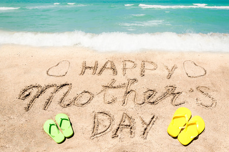Happy Mother's day background on the sandy beach near the ocean. Hand drawn lettering typography Imagens