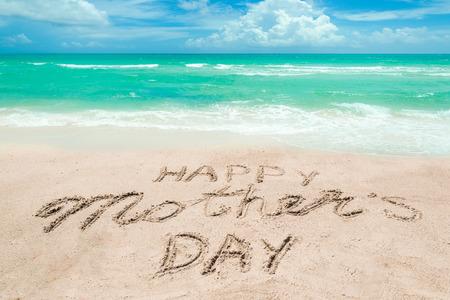 Fondo felice di festa della mamma sulla spiaggia sabbiosa vicino all'oceano. Tipografia di lettere disegnate a mano