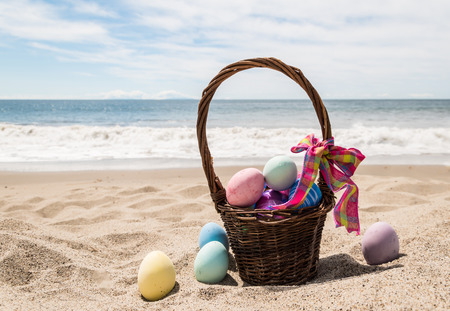 Beach Happy Easter background with basket and color eggs near ocean