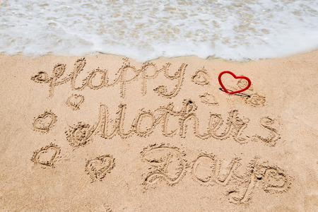 Happy Mother's day background on the sandy beach near the ocean with hearts. Hand drawn lettering typography 免版税图像