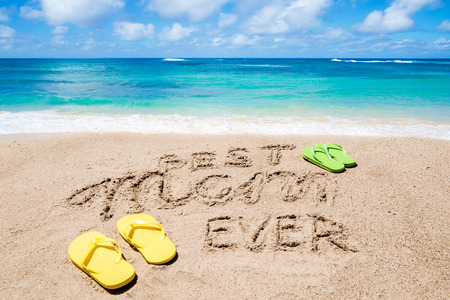 Happy Mother's day background on the sandy beach near the ocean. Sign Best Mom ever. Hand drawn lettering typography 免版税图像