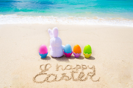 Happy easter background with bunny and color eggs on the ocean beach. Hand drawn Happy Easter typography lettering poster.