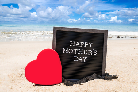 Happy Mothers day  with black board and heart on the sandy beach near the ocean. Stock Photo