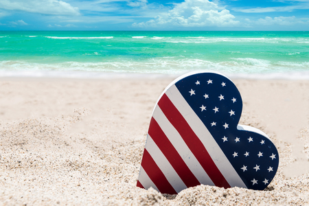 Patriotic USA background with American flag colored heart on the sandy beach near ocean