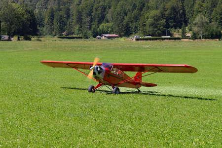 aircraft landing: Light red aircraft landing on a green meadow, transportation, outdoor