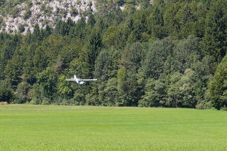 aircraft landing: Light white aircraft landing on a green meadow, transportation, outdoor