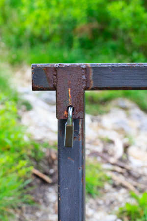 rusty fence: Close up of a padlock that close a rusty fence along a trekking path Stock Photo