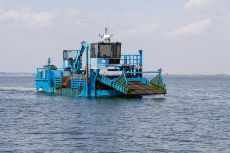 shipper: Close up of a blue dredger working on italian Po river lagoon. Industrial vehicle