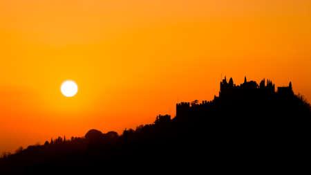 Castle silhouette at sundown. Italian panorama from Marostica. Orange sky