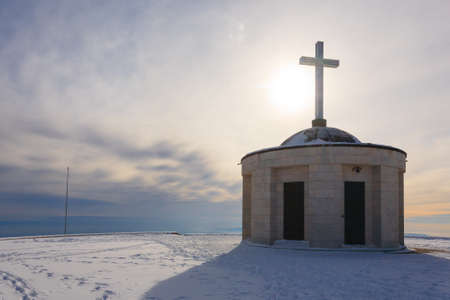 cristian: Cristian cross over a little church with sun in backlight. Italian winter panorama Stock Photo