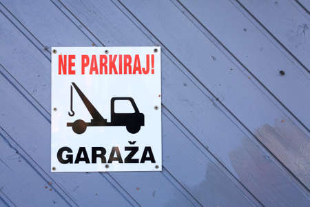 main entrance: No parking area sign in slovenian language. Tow truck sign. Stock Photo