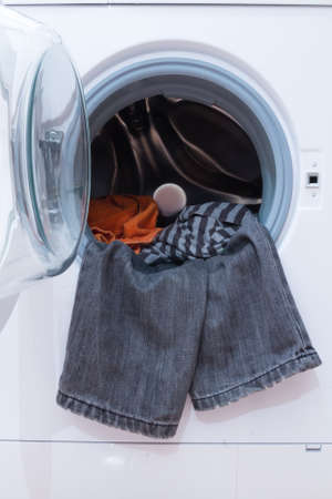 launder: A close up of a washing machine loaded with clothes. Household appliance.