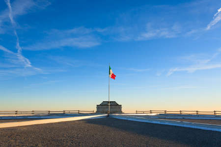 grappa: Italian flag on blue sky from first world war memorial in Monte Grappa, Italy. Italian Alps. Architecture Stock Photo