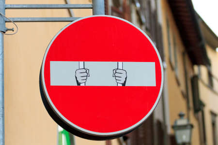 trepassing: Road sign with an hand that break out the signal, street art, metropolitan art