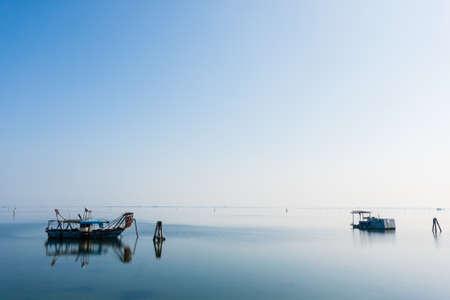 Fishing boats inside Po river lagoon, Italy. Italian landscape. Minimal water panorama