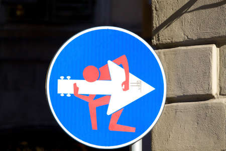 trepassing: Road sign with a man playing guitar on the signal, street art, metropolitan