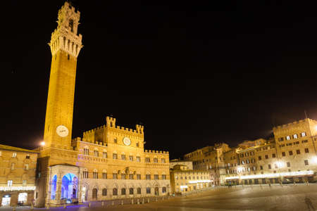 Night view of Campo Square (Piazza del Campo), Siena Palazzo Pubblico and Mangia Tower (Torre del Mangia) in Siena, Tuscany, Italy. Editorial