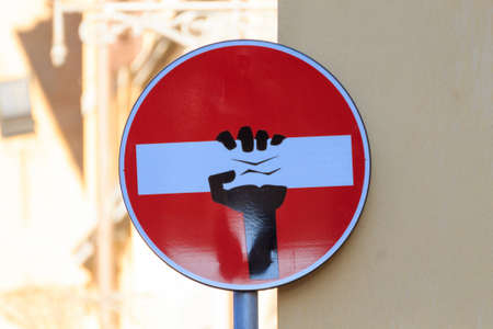 Road sign with an hand that break out the signal, street art, metropolitan art