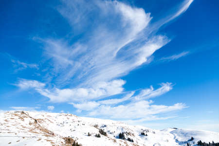 Winter landscape from Italian Alps. Beautiful clouds on blue sky. White snow Reklamní fotografie