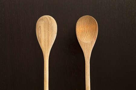 Wooden spoons on black table. Kitchen tools close up Reklamní fotografie