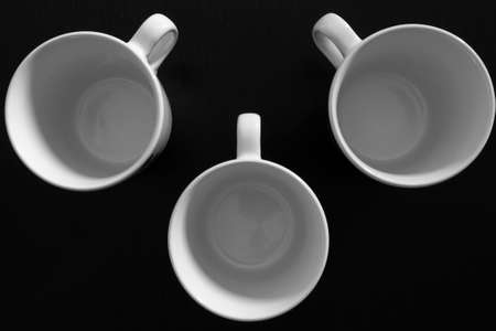Empty white cups on black wooden table. Kitchen tools close up
