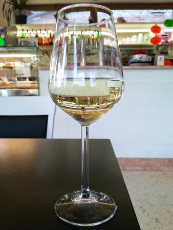 Glass of white wine close up with bar in background Reklamní fotografie