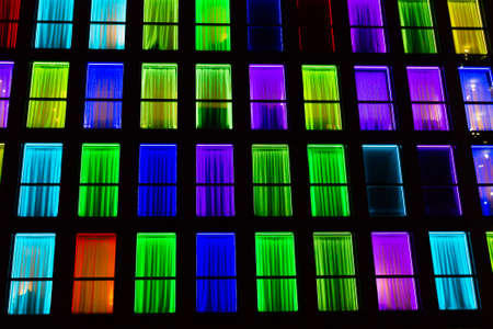 Colored windows texture.  Windows illuminated by neon lights background. Reklamní fotografie